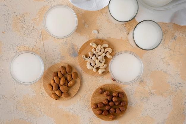 Sortierte nüsse wie mandel, acajoubaum, haselnuss und milch in einer glasflasche, gesunde nahrungsmittel