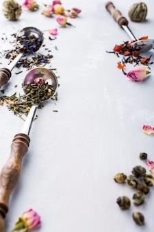 Sortierte teeblätter, schwarz, grün, rooibos und erdbeere in messlöffel