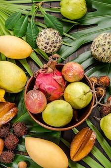 Sortierte thailändische tropische früchte auf einem dunklen hölzernen rustikalen hintergrund.