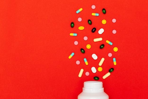 Sortierte verschiedene arten von pillen auf rotem hintergrund