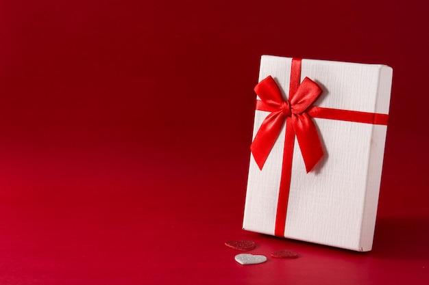 Sortierte weiße geschenkbox auf rotem hintergrund kopienraum