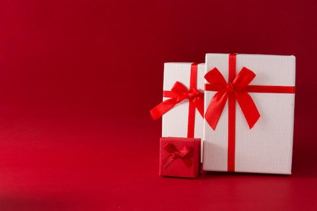 Sortierte weiße geschenkboxen auf rotem hintergrund kopienraum