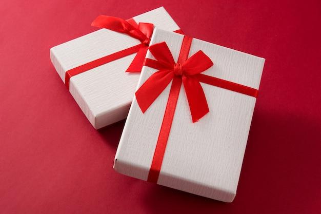 Sortierte weiße geschenkboxen auf rotem hintergrund