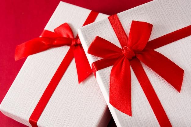 Sortierte weiße geschenkboxen auf rotem hintergrundabschluß oben