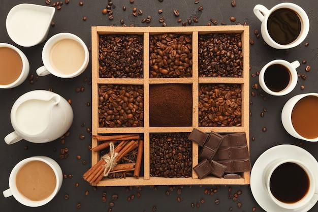Sortierter gemahlener kaffee und geröstete bohnen, gewürze und schokolade im quadratischen holzrahmen und verschiedene kaffeetassen auf grauem strukturiertem schiefer, draufsicht, kopienraum. template-design zum abwenden von cafés