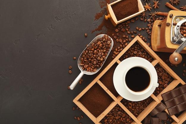 Sortierter gemahlener kaffee und geröstete bohnen in quadratischem holzrahmen auf grauem strukturiertem schiefer. draufsicht auf tasse mit getränke- und vintage-schleifer, kopierraum. vorlage zum abwenden von cafés oder coffeeshops