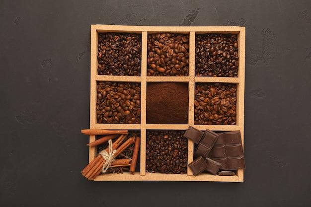 Sortierter gemahlener kaffee und geröstete bohnen in quadratischem holzrahmen und schalen auf grauem strukturiertem schiefer, draufsicht, kopienraum. vorlagendesign zum abwenden von cafés oder coffeeshops