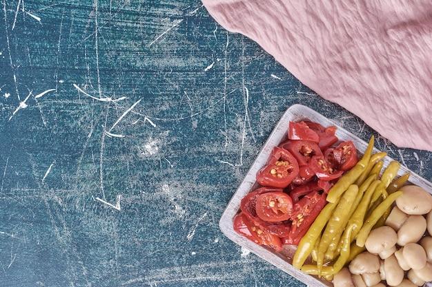 Sortiertes eingelegtes gemüse auf weißem teller mit tischdecke.