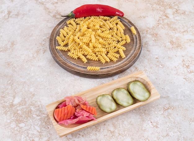 Sortiertes essiggurkentablett neben einem brett mit paprikapfeffer und rohem teigwarenstapel auf marmoroberfläche.