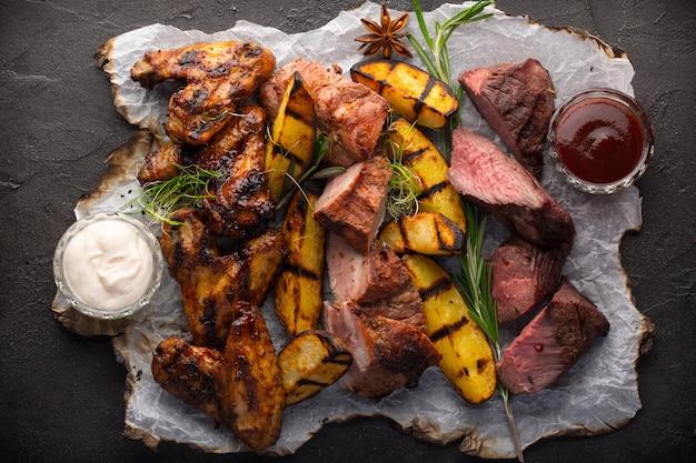 Sortiertes gegrilltes fleisch und kartoffeln auf schwarzem hintergrund