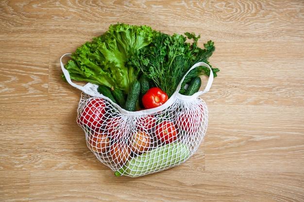 Sortiertes gemüse im lebensmittelnetz-strangbeutel auf hölzernem hintergrund
