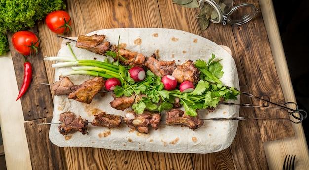 Sortiertes köstliches gegrilltes fleisch mit gemüse auf weißem plattenpicknicktisch für familienbbq-partei