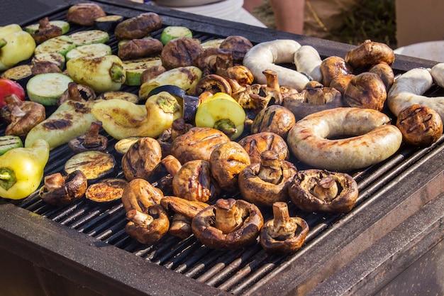 Sortiertes köstliches gegrilltes fleisch mit gemüse über den kohlen auf einem grill