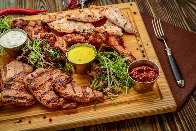 Sortiertes köstliches gegrilltes fleisch und gemüse mit frischem salat und bbq-soße auf schneidebrett auf hölzernem hintergrund. große reihe von warmen fleischgerichten