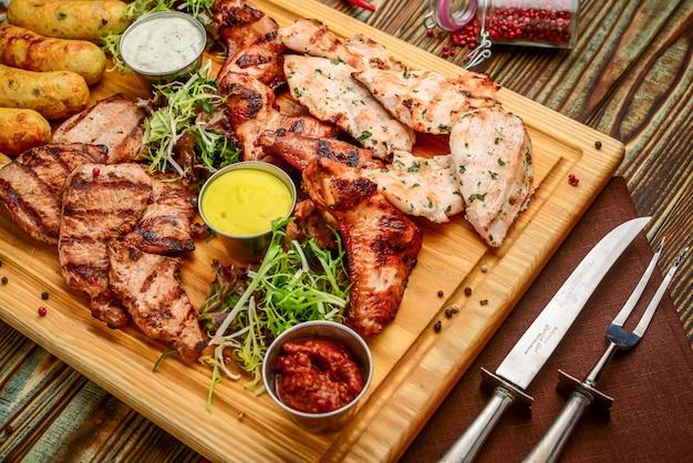 Sortiertes köstliches gegrilltes fleisch und gemüse mit frischem salat und bbq-soße auf schneidebrett auf woode