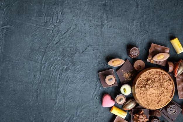 Sortiertes schokoladen- und kakaopulver auf schwarzem