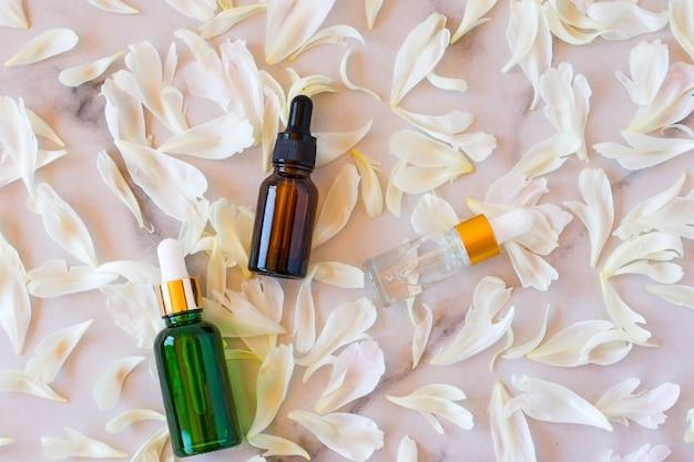 Sortiment an bio-spa-kosmetik mit pflanzlichen inhaltsstoffen. serum zur hautpflege. naturkosmetik in glasflaschen mit pipette auf marmorhintergrund.