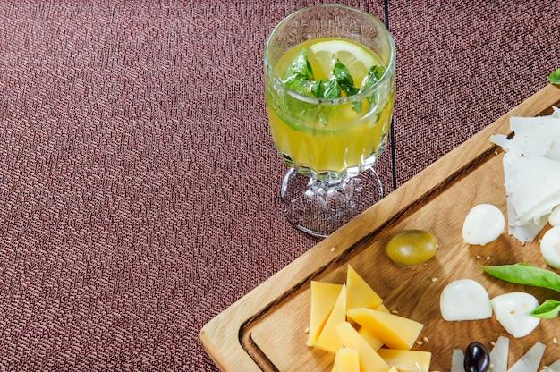 Sortiment des käses auf einem rustikalen schneidebrett-holzhintergrund.