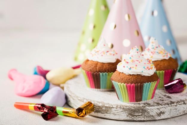 Sortiment mit glasierten muffins und partydekorationen