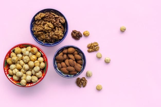 Sortiment mix aus nüssen, haselnüssen, mandeln, walnüssen in schalen. flachgelegt, draufsicht