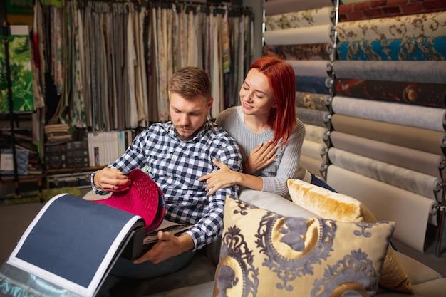 Sortiment. paar, das textil zu hause dekorationsgeschäft, geschäft wählt. herstellung von inneneinrichtung während der quarantäne. glücklicher mann und frau, junge familie sehen verträumt aus, fröhliche materialauswahl.