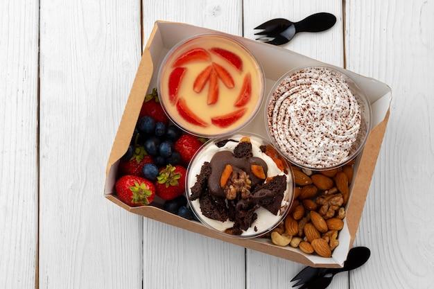 Sortiment von desserts im kasten auf hölzernem hintergrund