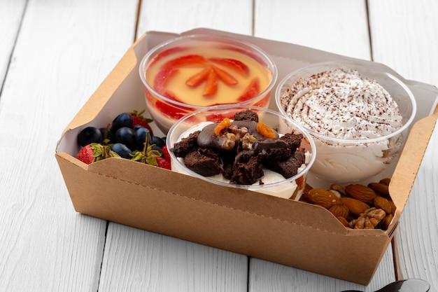 Sortiment von desserts in kisten auf weißem holzhintergrund