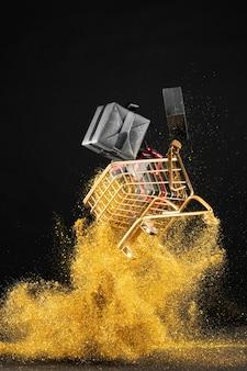 Sortiment von schwarzen freitaggeschenken im einkaufswagen mit goldenem glitzer