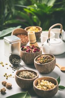 Sortiment von trockenem tee in kokosnussschalen.