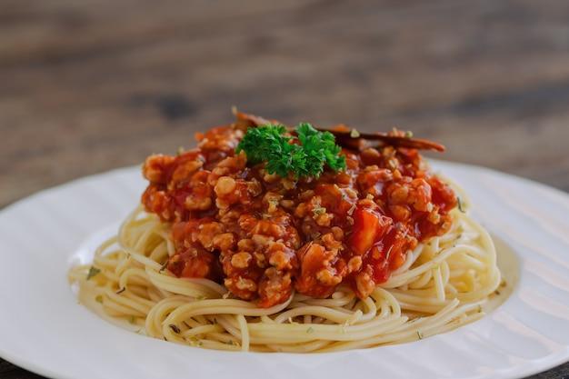 Soße der spaghetti-bolognese mit rindfleisch oder schweinefleisch, käse, tomaten und gewürze auf weißer platte auf w