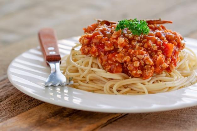 Soße des spaghettis bolognese mit rindfleisch oder schweinefleisch, käse, tomaten und gewürzen auf weißer platte