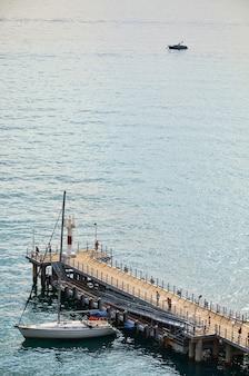 Sotschi, russland. segelyacht am pier gegen das ruhige meer und ein kleines boot in der ferne.