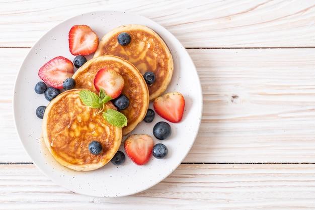 Souffle pfannkuchen mit frischen blaubeeren, frischen erdbeeren und honig