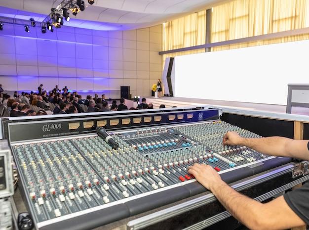 Sound operator arbeitet mit fernbedienung auf der konferenz