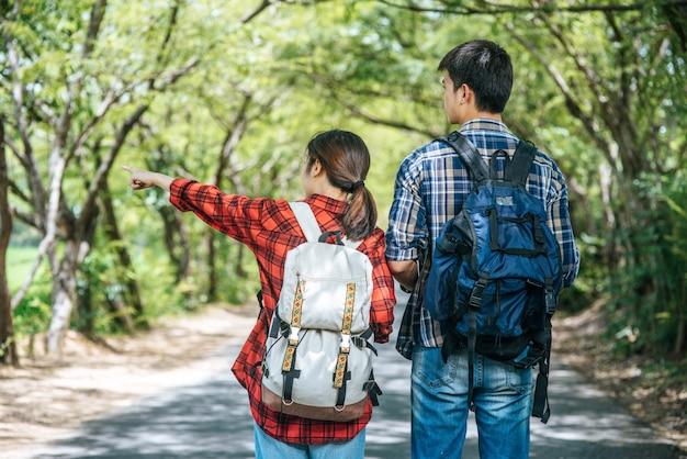 Sowohl männliche als auch weibliche touristen sehen die karte auf der straße.
