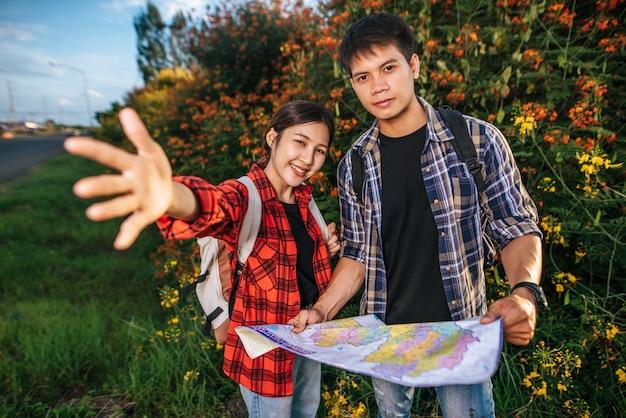 Sowohl männliche als auch weibliche touristen tragen einen rucksack, der in einem blumengarten steht.