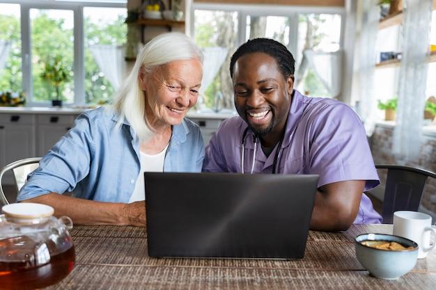 Sozialarbeiter, der mit einer älteren frau auf einem laptop schaut