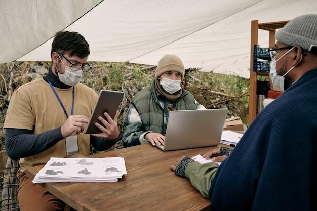Sozialarbeiter in masken, die am tisch sitzen und geräte benutzen, während sie mit einem schwarzen migranten unter einem zelt sprechen