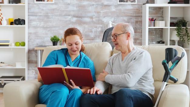 Sozialarbeiter liest einem alten und behinderten mann vor, der auf einem sofa in einem hellen pflegeheim sitzt