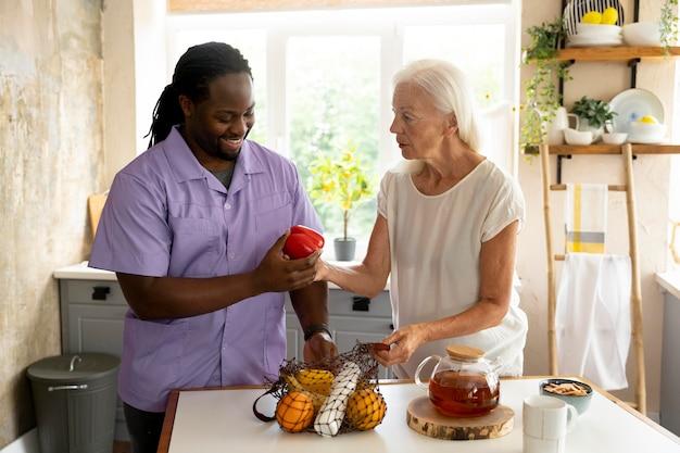 Sozialarbeiterin, die mit einer älteren frau essen macht