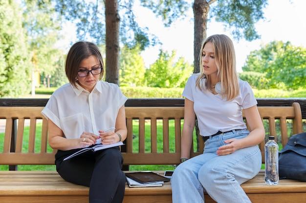 Sozialarbeiterin, die mit mädchen teenager spricht, die interviews im notizbuch schreibt, frauen, die auf der bank im park sitzen?