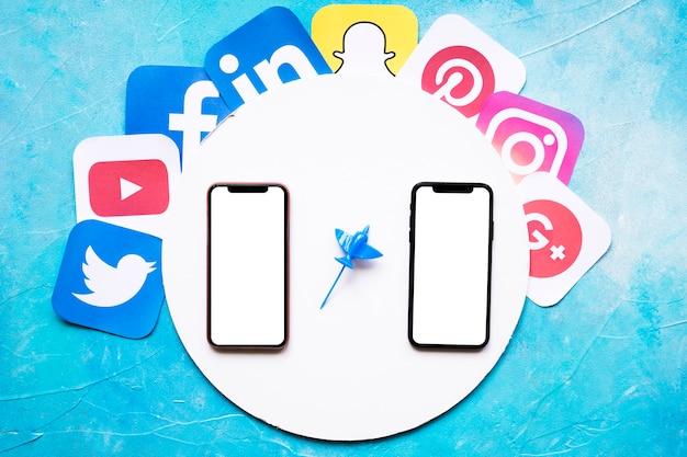 Soziale bewegliche anwendungsikonen um den kreisförmigen weißen rahmen mit mobiltelefon zwei gegen blauen hintergrund