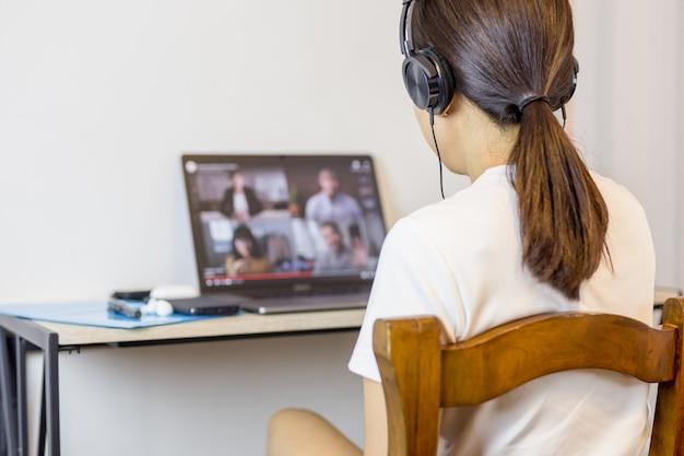 Soziale distanzierende frau, die kopfhörer während des gruppenvideoanrufs mit freunden trägt.