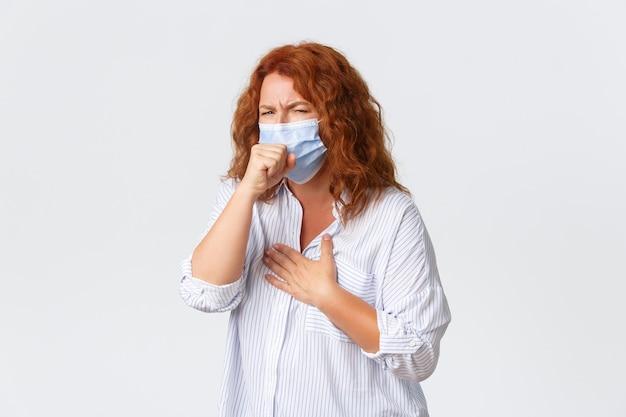 Soziale distanzierung, coronavirus-selbstquarantäne und personenkonzept. porträt der kranken rothaarigen frau mittleren alters, die hustet, medizinische maske trägt, sauren hals hat, krankheitssymptome
