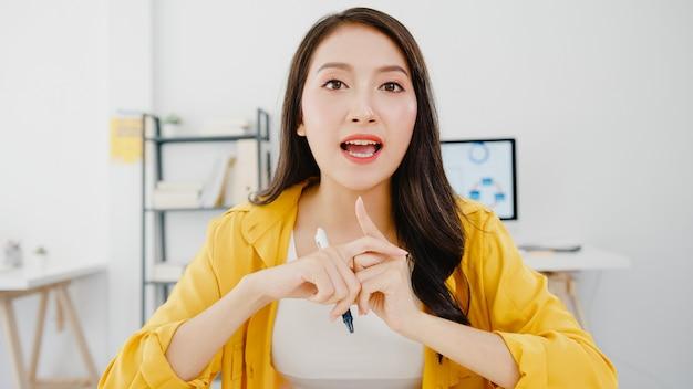 Soziale distanzierung der asiatischen geschäftsfrau in einer neuen normalen situation zur virenprävention, die die kamerapräsentation an freunde über plan in videoanruf während der arbeit im büro betrachtet. lebensstil nach dem koronavirus.