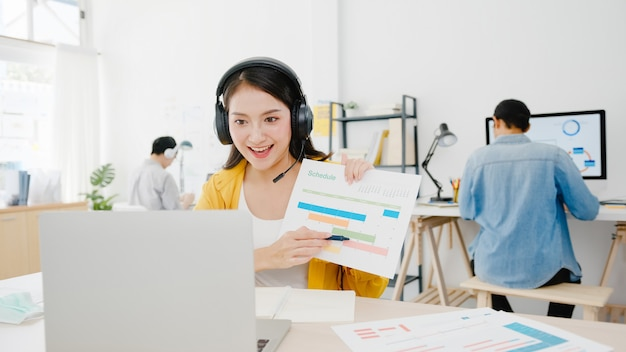 Soziale distanzierung der asiatischen geschäftsfrau in einer neuen normalen situation zur virenprävention während der verwendung einer laptop-präsentation für kollegen über den plan eines videoanrufs während der arbeit im büro. leben nach dem corona-virus.