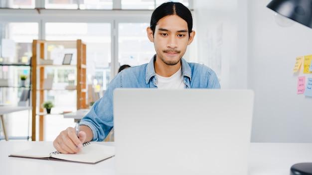 Soziale distanzierung des geschäftsmanns in asien in einer neuen normalen situation zur virenprävention unter verwendung einer laptop-präsentation an einen kollegen über einen plan in einem videoanruf während der arbeit im home office. lebensstil nach dem koronavirus.