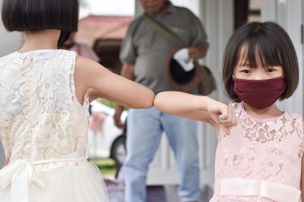 Soziale distanzierung. zwei kinder stoßen ellbogen neuen roman gruß. freunde demonstrieren, um die ausbreitung des coronavirus zu vermeiden.