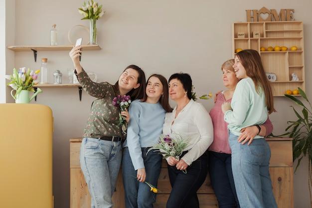 Soziale weibliche versammlung, die ein foto macht