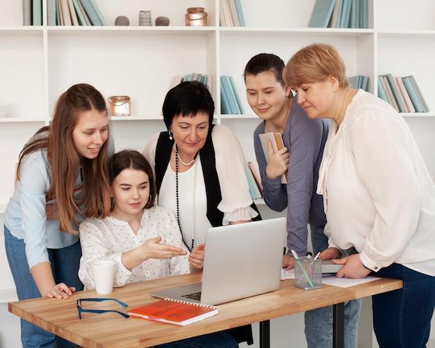 Soziale weibliche versammlung, die einen laptop betrachtet